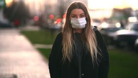 Girl in a medical mask on the background of the city. Coronavirus. Prevention of viral diseases