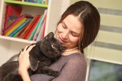 Girl medical mask on her face is holding British cat breed.toxoplasmosis protection against cat infection for humans stock photography