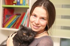 Girl medical mask on her face is holding British cat breed.toxoplasmosis protection against cat infection for humans stock images