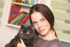 Girl medical mask on her face is holding British cat breed.toxoplasmosis protection against cat infection for humans royalty free stock photography