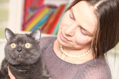 Girl medical mask on her face is holding British cat breed.toxoplasmosis protection against cat infection for humans stock image