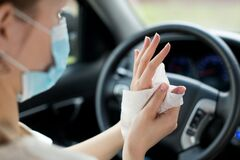 Girl in a medical mask rubs her hands with an antiseptic wipe in a car