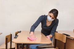 Girl in a medical mask washes tables in a school class during the quarantine period