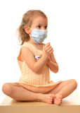 Girl is in a medical with a thermometer. Little girl in a non-permanent medical mask with a thermometer Royalty Free Stock Images