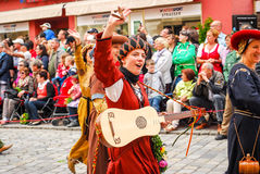 Girl  in medieval costume waves to the crowds Stock Images