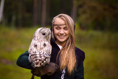Girl in medieval dress is holding an owl on her arm Stock Image