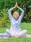 Girl meditate on rug green grass meadow nature background. Woman relaxing practicing meditation. Every day meditation stock photography