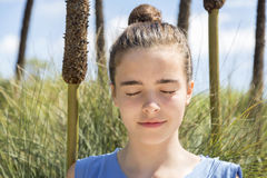 Girl meditates in front of a reed field Royalty Free Stock Photography