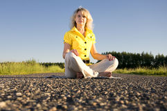 Girl meditates on highway middle in rural Stock Photography