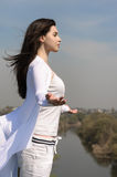 Girl meditates on a hill against the blue sky. She stands her arms to the side and her hair fluttering in the wind. She is wearing in a white loose-fitting Stock Photography