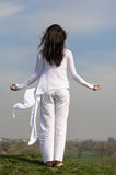 Girl meditates on a hill against the blue sky. She stands her arms to the side and her hair fluttering in the wind. She is wearing in a white loose-fitting Royalty Free Stock Photos
