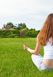 Girl meditates on lawn in garden. Stock Photo