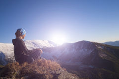 Girl meditates in the mountains. Stock Photos