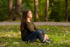 The girl meditates in park. The young beautiful girl with long hair, meditates in autumn park Royalty Free Stock Photo