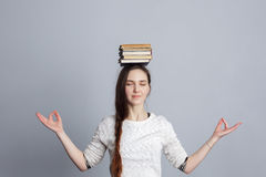 Girl meditates with a pile of books on head. Royalty Free Stock Images
