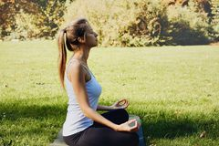 Girl meditates while practicing yoga outdoors in park royalty free stock images