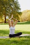 Girl meditates while practicing yoga outdoors in park royalty free stock image