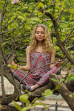 The girl meditates sitting on tree in the garden Stock Photo