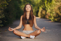 The girl meditates before sports. Stock Photos