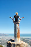 Girl meditates on top of column in mountains Stock Image