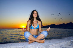 Girl meditating. Woman meditating at sunset on the background of the sea stock photo