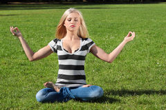 A girl meditating. In yoga postures outdoors Stock Photo