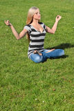 A girl meditating. In yoga postures outdoors Royalty Free Stock Photo