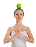 Girl meditating with apple on her head Stock Image