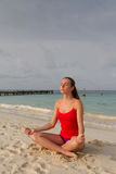 Girl meditating at the beach Stock Photography