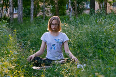 Girl meditating in city park. Teenage girl meditating in lotus position in citypark Royalty Free Stock Image