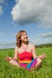 Girl meditating on grass Stock Photo