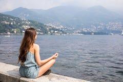 Girl meditating by the lake Stock Photo