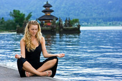 Girl meditating at the lake on Bali Stock Image