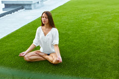 Girl meditating in lotus posture. Yoga. Beautiful young healthy girl meditating on the grass in park in lotus posture with her hands turn up to the sky. She is Stock Image