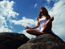 Girl meditating on a mountaintop. In the background of blue sky stock images