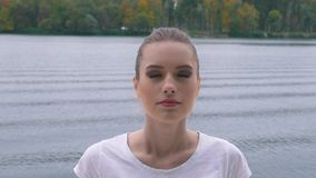 The girl is meditating near the lake stock video footage