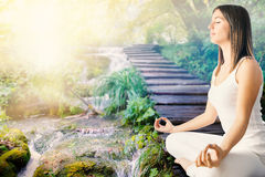 Girl meditating next to stream in forest. Stock Photo