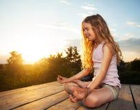 Girl meditating. Outdoors. Child practicing yoga Stock Image