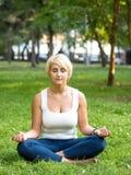 Girl meditating in park Stock Photo