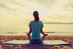 Girl meditating in pose of lotus on beach Royalty Free Stock Photography