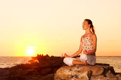 Girl meditating on rocks. Stock Photography