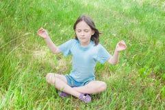 Girl meditating. Summer girl child sitting on the grass meditating Stock Photography