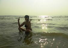 Girl meditating at sunset. A girl in a lotus position at sunset, sits in the Gulf of Siam at low tide Stock Images