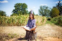 Girl meditating on a tump in a meadow Stock Images