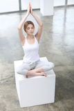 Girl meditating. On a white platform Royalty Free Stock Photo