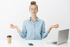 Girl meditating at work sitting in lotus pose with nirvana orbs near laptop and smartphone trying relax and get rid of. Pressure and stress posing calm and royalty free stock image