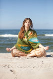 Girl meditating. Young beautiful girl meditating on beach in lotus position Stock Photo
