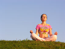 Girl meditation blue sky. Sunset royalty free stock image