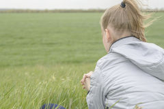 Girl meditation Field. Girl meditating sitting on the green grass in the field Royalty Free Stock Photos