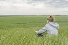 Girl meditation Field. Girl meditating sitting on the green grass in the field Royalty Free Stock Photography